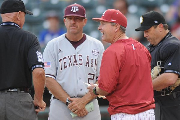 Texas A&M coach Rob Childress, left, and Arkansas coach Dave Van Horn meet with umpires prior to a game Friday, May 9, 2014 at Baum Stadium in Fayetteville. Childress was an assistant coach to Van Horn for 10 seasons.