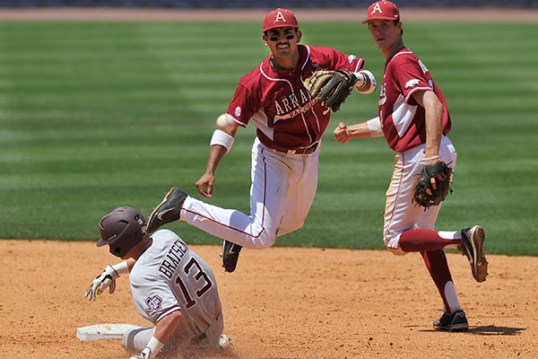 Arkansas shortstop Michael Bernal turns a double play during the Razorbacks' game against Texas A&M on Tuesday at the SEC Tournament in Hoover, Ala.