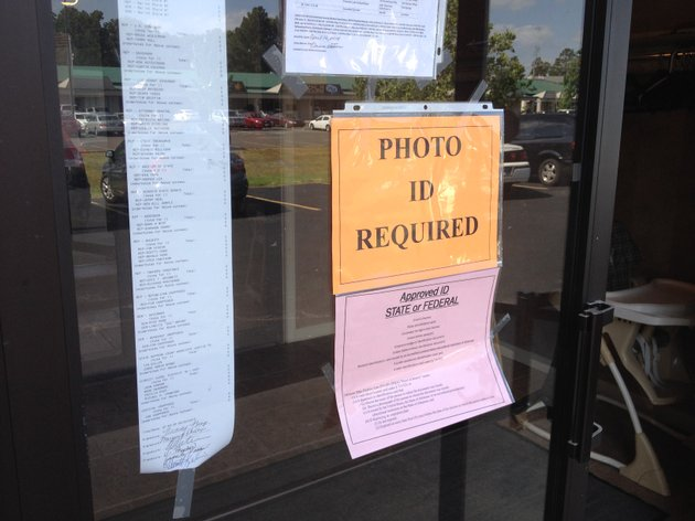a-sign-on-the-door-at-a-polling-site-at-first-church-of-the-nazarene-in-hot-springs-informs-voters-they-must-show-id-to-cast-a-ballot