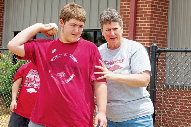 caleb-cook-left-gets-some-pointers-from-special-olympics-arkansas-director-sally-paine-before-practicing-throwing-a-softball-in-preparation-for-the-summer-games