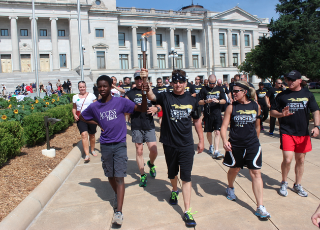 special-olympics-athlete-eli-falls-15-left-helps-escort-the-2014-special-olympics-arkansas-summer-games-torch-from-the-arkansas-state-capitol-thursday