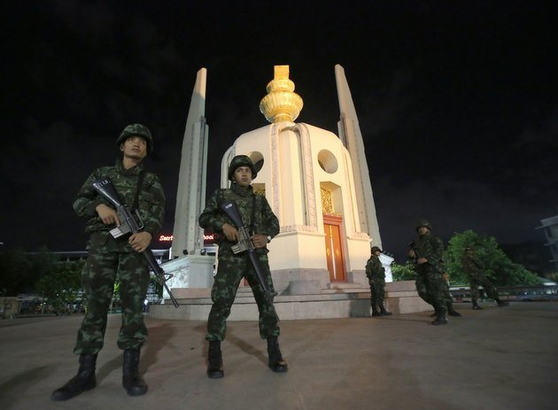 thai-soldiers-stand-guard-in-front-of-the-democracy-monument-after-the-coup-thursday-may-22-2014-in-bangkok-thailand-thailands-military-seized-power-thursday-in-a-bloodless-coup-dissolving-the-government-suspending-the-constitution-and-dispersing-groups-of-protesters-from-both-sides-of-the-countrys-political-divide-who-had-gathered-in-bangkok-and-raised-fears-of-a-violent-showdown