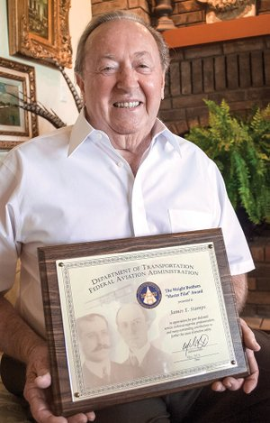 Jim Stamps, 83, at his home in Russellville, holds The Wright Brothers Master Pilot Award he received May 10 for his dedication and service to aviation safety. The honor is given to pilots who have 50 or more continuous years as a pilot without incident.