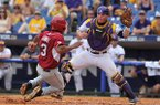 LSU catcher Kade Scivicque tags out Arkansas shortstop Michael Bernal at home plate during a SEC Tournament game Saturday, May 24, 2014 at Hoover Metropolitan Stadium in Hoover, Ala.
