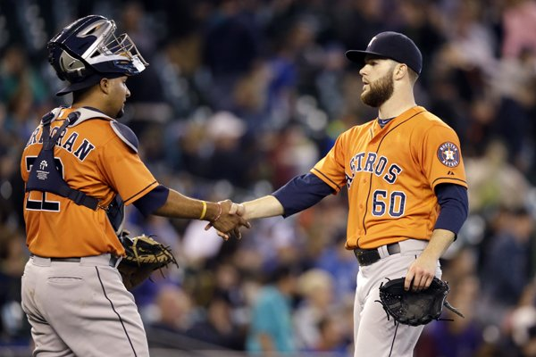Houston Astros starting pitcher Dallas Keuchel (60) shakes hands with catcher Carlos Corporan after throwing a complete game against the Seattle Mariners in a baseball game Sunday, May 25, 2014, in Seattle. The Astros won 4-1. (AP Photo/Elaine Thompson)