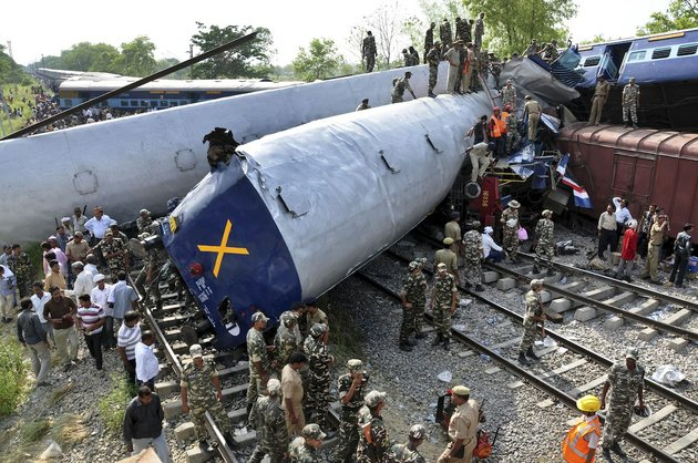 indian-officials-and-rescuers-stand-near-the-wreckage-after-the-gorakhpur-express-passenger-train-slammed-into-a-parked-freight-train-chureb-near-basti-uttar-pradesh-state-india-monday-may-26-2014-according-to-officials-dozens-were-killed