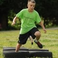NWA Media/ANDY SHUPE - Gavin Goddard, 11, runs through tires while competing in an obstacle course d...