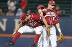 Arkansas outfielders Joe Serrano, left, Tyler Spoon, right, and Andrew Benintendi celebrate Arkansas' win over Liberty in an NCAA college baseball tournament regional game in Charlottesville, Va., Friday, May 30, 2014. Arkansas won 3-2. (AP Photo/Steve Helber)