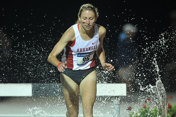 Arkansas runner Grace Heymsfield leads the pack as she makes the water jump in the women's 3,000 meter steeplechase Friday at the 2014 NCAA Track & Field West Preliminaries at John McDonnell field in Fayetteville.