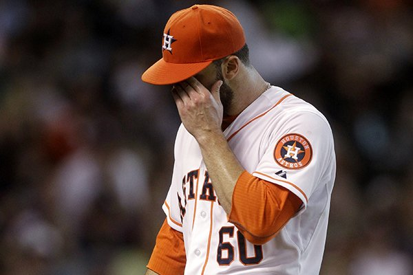 Houston Astros pitcher Dallas Keuchel reacts after walking in two runs during the fifth inning of a baseball game against the Baltimore Orioles, Saturday, May 31, 2014, in Houston. (AP Photo/Patric Schneider)