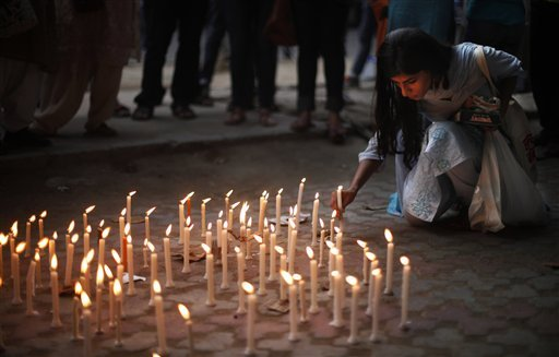 an-activist-places-a-candle-on-a-pavement-during-a-candle-lit-vigil-to-protest-against-the-gang-rape-of-two-teenage-girls-in-new-delhi-india-saturday-may-31-2014-police-arrested-a-third-suspect-and-hunted-for-two-others-saturday-in-the-gang-rape-and-slaying-of-two-teenage-cousins-found-hanging-from-a-tree-in-katra-village-in-the-northern-indian-state-of-uttar-pradesh-a-case-that-has-prompted-national-outrage