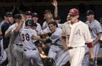 Virginia players celebrate teammate Mike Papi (38) after scoring in front of Arkansas pitcher Zach Jackson, right, during an NCAA college baseball regional tournament game, Sunday, June 1, 2014, in Charlottesville, Va. (AP Photo/Andrew Shurtleff)