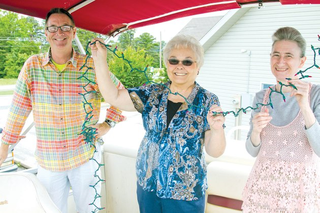 from-left-kevin-thomas-joann-wanat-and-vicki-miller-of-the-greers-ferry-chamber-of-commerce-string-lights-on-a-boat-in-preparation-for-the-lighted-boat-parade-contest-coming-up-june-14