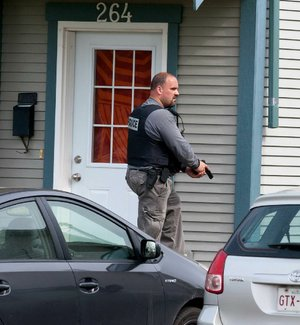 A Royal Canadian Mounted Police officer searches around a house in Moncton, New Brunswick, on Thursday in the hunt for a heavily armed gunman suspected of killing three Mounties and injuring two others.