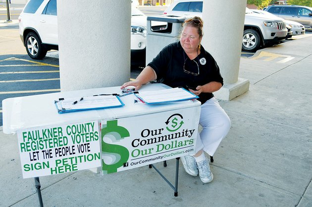 a-woman-who-is-an-employee-of-national-ballot-access-and-declined-to-give-her-name-mans-a-table-outside-walgreens-on-oak-street-in-downtown-conway-she-was-gathering-signatures-for-the-our-community-our-dollars-campaign-which-seeks-about-25000-signatures-in-faulkner-county-to-get-the-wet-dry-issue-on-the-nov-4-ballot-the-decline-to-sign-campaign-is-working-against-the-effort
