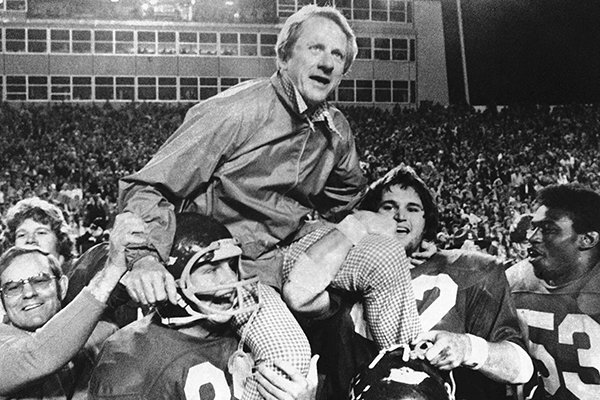 In this Dec. 6, 1975, file photo, Arkansas coach Frank Broyles is carried from the field by players Teddy Barnes, left, and Richard LaFargue (52) following his team's 30-6 NCAA college football game victory over Texas A&M in Little Rock. (AP Photo/Ferd Kaufman, File)