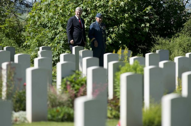 canadian-prime-minister-stephen-harper-speaks-with-major-general-richard-rohmer-as-he-walks-through-the-canadian-military-cemetery-friday-june-6-2014-in-beny-sur-mer-france