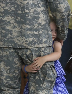 Arkansas Democrat-Gazette/STATON BREIDENTHAL --6/6/14-- Marlie Echols, 4, holds on to her father, Specialist Joseph Echols of Paragould, Friday at Camp Robinson following a deployment ceremony for the 1038th Horizontal Construction Company. The 160 soldiers are leaving next week for Ft. Bliss as part of a nine-month deployment to Kuwait.
