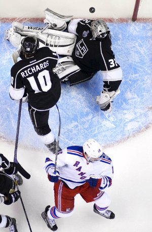 New York Rangers center Derick Brassard, bottom, celebrates after scoring past Los Angeles Kings goalie Jonathan Quick, top, and center Mike Richards during the second period of Game 2 in the NHL Stanley Cup Final hockey series in Los Angeles, Saturday, June 7, 2014.