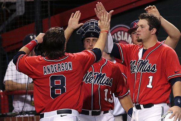 Mississippi infielder Austin Anderson (8) is greeted at the dugout after scoring on an RBI double by Will Allen in the first inning of an NCAA college baseball tournament super regional game against Louisiana Lafayette in Lafayette, La.,Sunday, June 8, 2014. (AP Photo/Gerald Herbert)