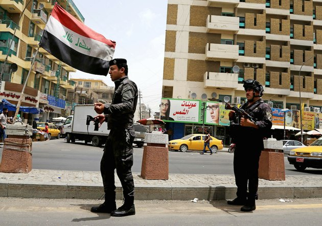 iraqi-federal-policemen-stand-guard-at-a-checkpoint-in-baghdad-iraq-on-wednesday-june-11-2014-the-iraqi-government-has-tightened-its-security-measures-after-a-stunning-assault-that-exposed-iraqs-eroding-central-authority-al-qaida-inspired-militants-overran-much-of-mosul-on-tuesday-seizing-government-buildings-pushing-out-security-forces-and-capturing-military-vehicles-as-thousands-of-residents-fled-the-iraqi-second-largest-city