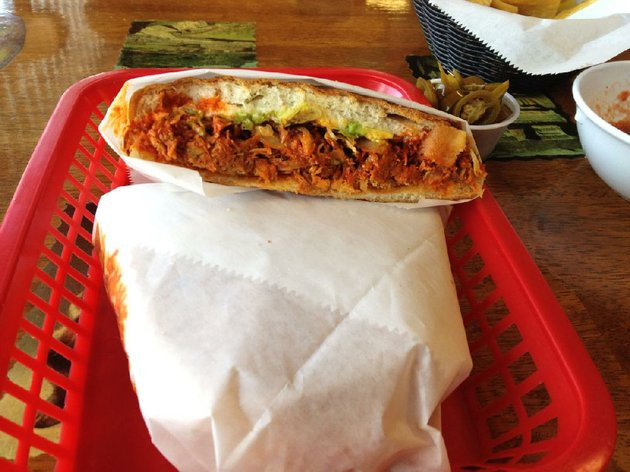 the-torta-pierna-enchilada-at-north-little-rocks-tortas-mexico-features-shredded-pork-in-a-red-sauce-with-lettuce-mayonnaise-tomatoes-onions-avocado-and-jalapeno-peppers-on-an-enormous-bun