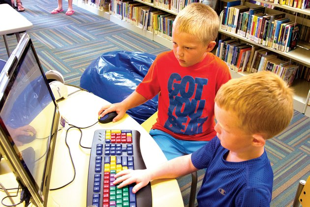 colby-boyd-left-and-corey-boyd-play-on-a-computer-at-the-newly-renovated-mary-i-wold-cleburne-county-library-in-heber-springs-the-facilitys-renovations-include-defined-areas-for-children-and-genealogy-as-well-as-computers-and-outlets-to-accommodate-patrons-the-library-opened-june-4-and-has-already-seen-checkouts-triple