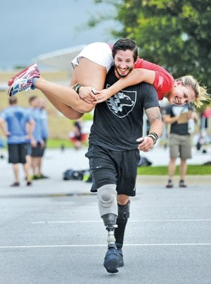 "STAFF PHOTO SAMANTHA BAKER • @NWASAMANTHA Nicholas Perales, retired Marine Cpl., who sustain numerous injuries during his time in Afghanistan including a right leg amputation ""buddy carries"" workout partner Jessica Mesko on June 7, 2014 at Arvest Ballpark in Springdale during the 2014 Heroes WOD."