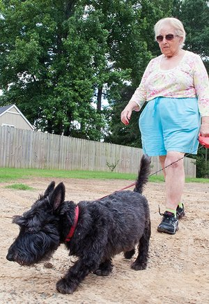 Barbara Moeller takes Barney, her Scottish terrier, for a stroll on the Tucker Creek Walking/Bike Trail in Conway. The Conway City Council on Tuesday approved allocating $25,000 from Advertising and Promotion Commission funds to match $25,000 the city won in an online contest in 2013. Conway's first dog park will be built on almost 4 acres at the Don Owen Recreation Complex on Lower Ridge Road.