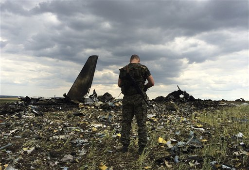 a-pro-russian-fighter-guards-the-site-of-remnants-of-a-downed-ukrainian-army-aircraft-il-76-at-the-airport-near-luhansk-ukraine-saturday-june-14-2014-pro-russian-separatists-shot-down-the-military-transport-plane-saturday-in-the-countrys-restive-east-killing-all-49-service-personnel-on-board-ukrainian-officials-said