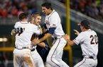 Virginia's Mike Papi, center, is mobbed by teammates after his two-out double in the bottom of the ninth inning knocked across the winning run. Virginia won, 2-1. University of Virginia played a baseball game against Ole Miss in the fourth game of the College World Series at TD Ameritrade Park in Omaha, Neb., on June 15, 2014. (AP Photo/Omaha World-Herald, Brynn Anderson)