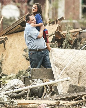 A man carries a girl after she was pulled from the basement of her destroyed home in Pilger, Neb., on Monday. A hospital spokesman said at least one person is dead and at least 16 more are in critical condition after two tornadoes swept through northeast Nebraska.