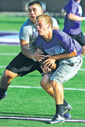 STAFF PHOTO ANDY SHUPE Myles Koch, right, Fayetteville sophomore, makes a catch Monday in front of junior Jonathan Betancourt during a 7-on-7 tournament for the Bulldogs' offensive line corps at Harmon Stadium in Fayetteville.