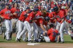 Mississippi players celebrate their 2-1 win over Texas Tech with teammate John Gatlin (36), who hit the single that scored Aaron Greenwood in the ninth inning, in an NCAA baseball College World Series elimination game in Omaha, Neb., Tuesday, June 17, 2014. (AP Photo/Ted Kirk)