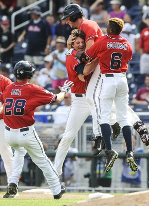 Ole Miss' Aaron Greenwood (second from right) celebrates scoring the winning run against Texas Tech on Tuesday with Brantley Bell (28), John Gatlin (second from left) and Errol Robinson (6).