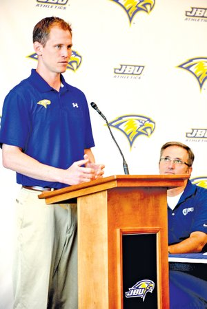 Staff Phoot Graham Thomas Jason Beschta, new John Brown University men's basketball coach, speaks during a news conference Tuesday as JBU Vice President of Student Development Dr. Steve Beers, right, looks on at the Simmons Great Hall on the campus of JBU.