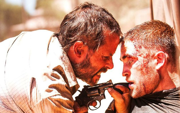 eric-guy-pearce-convinces-a-gut-shot-rey-robert-pattinson-to-help-him-in-his-quest-to-retrieve-his-stolen-car-in-the-dystopian-thriller-the-rover