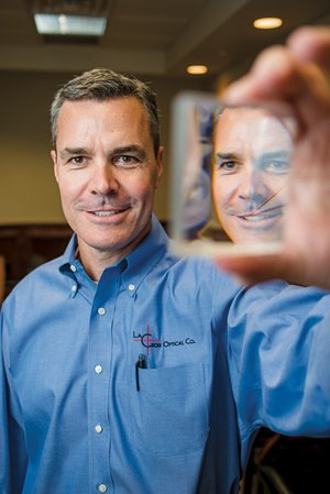 Kirk Warden is co-founder of the Arkansas Photonics Industry Alliance and executive vice president of LaCroix Optical Co. in Batesville, which manufactures custom lenses for a variety of defense, medical and other uses. He holds a large prism made by the company.