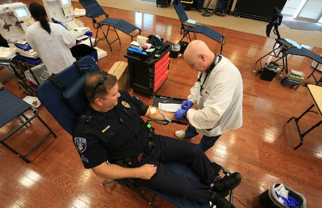 arkansas-democrat-gazetterick-mcfarland-north-little-rock-police-officer-todd-humphries-has-his-blood-drawn-by-rich-armstrong-with-the-american-red-cross-at-the-hays-senior-center-on-june-20-humphries-was-participating-in-the-battle-of-the-badge-which-challenges-police-and-firefighters-to-out-do-each-other-in-numbers-giving-blood