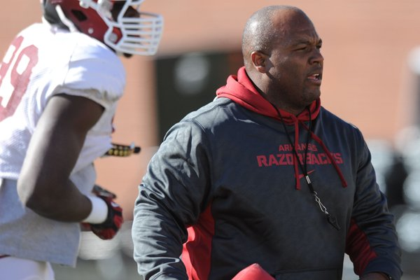 Arkansas defensive backs coach Clay Jennings directs his players during practice Thursday, March 20, 2014, at the UA practice field in Fayetteville.