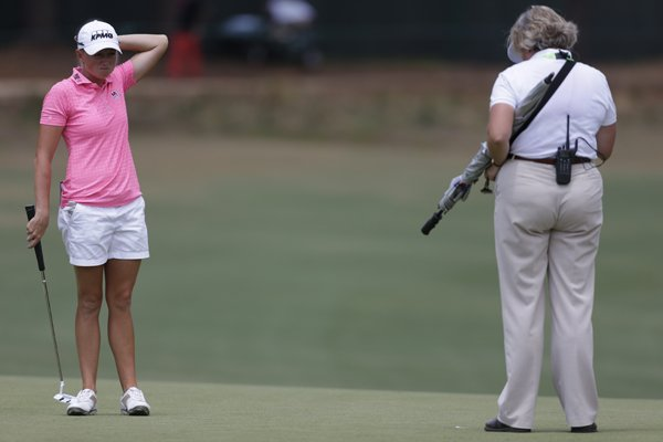 Stacy Lewis, left, waits for an official's ruling on the third hole during the third round of the U.S. Women's Open golf tournament in Pinehurst, N.C., Saturday, June 21, 2014. (AP Photo/Bob Leverone)