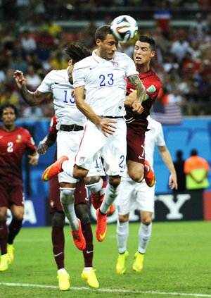 United States' Fabian Johnson (23) heads the ball away from Portugal's Cristiano Ronaldo, right, during the group G World Cup soccer match between the USA and Portugal at the Arena da Amazonia in Manaus, Brazil, Sunday, June 22, 2014. (AP Photo/Paulo Duarte)