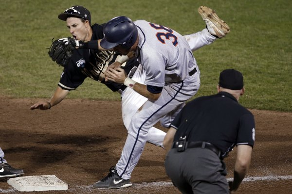 Vanderbilt third baseman Tyler Campbell, rear, collides with Virginia's Mike Papi as he tags out Papi in the ninth inning of Game 2 of the best-of-three NCAA baseball College World Series finals in Omaha, Neb., Tuesday, June 24, 2014. (AP Photo/Nati Harnik)