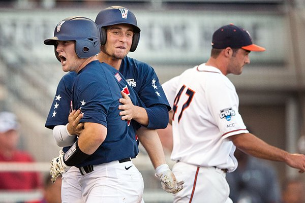 Vanderbilt's Jason Delay, left, and Rhett Wiseman celebrate after they scored on Tyler Campbell's double that scored three runs in the 9-run third inning. UVA relief pitcher Whit Mayberry (47) is at right. The University of Virginia played a baseball game against Vanderbilt in the first game of the championship finals of the College World Series at TD Ameritrade Park in Omaha, Neb., on Monday, June 23, 2014. (AP Photo/The World-Herald, Ryan Soderlin)