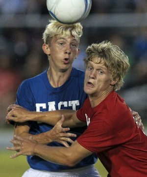 Harrison's Andrew Matthews (right) of the West All-Stars defends against the East's Dusty Gibson of Nettleton in the boys soccer game Wednesday night in Conway.