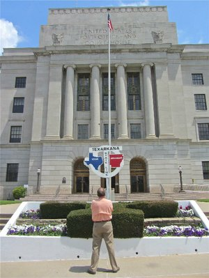 Visitors to Texarkana can stand in Arkansas and Texas outside the U.S. Post Office and Courthouse on the state line.