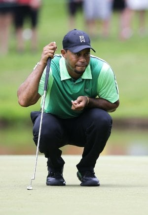 Tiger Woods lines up his putt on the sixth green during the first round of the Quicken Loans National on Thursday at Congressional Country Club in Bethesda, Md. Woods finished with a 4-over-par 74 in his first tournament since having back surgery.