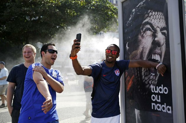 a-us-soccer-fan-pretends-uruguay-forward-luis-suarez-is-biting-him-as-he-takes-a-photo-thursday-in-front-of-an-adidas-advertisement-featuring-suarez-near-copacabana-beach-in-rio-de-janeiro-suarez-was-banned-by-fifa-from-all-soccer-for-four-months-and-fined-112000-for-biting-an-italian-player-during-uruguays-1-0-victory-tuesday