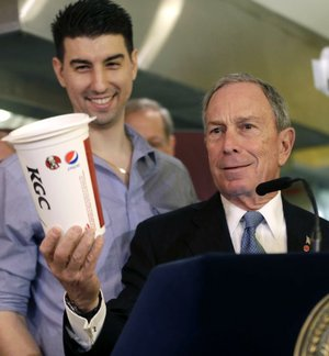 FILE - In this March 12, 2013 file photo, New York City Mayor Michael Bloomberg, right, looks at a 64oz cup, as Lucky's Cafe owner Greg Anagnostopoulos stands behind him, during a news conference at the cafe in New York. The New York Court of Appeals ruled Thursday, June 26, 2014 that the city's health department overstepped its bounds when it restricted the size of sodas. The court is siding with a lower court that overturned the 2012 ban.  (AP Photo/Seth Wenig, File)