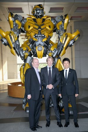 Vice Chairman of Paramount Rob Moore, director Michael Bay and Pangu Hotel general manager Norman Song pose for photos beside a Bumblebee Autobot at Beijing's Pangu Hotel recently.